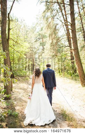 Bride and groom in a forest. Sensual photo of the groom and bride Wedding photo concept. Bridal bouquet and boutonniere. Wedding photo concept. Summer wedding. Wedding dress with open back