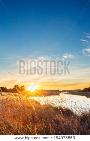 Sunset On The River Bank Covered With Grass Meadow