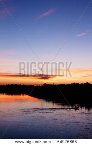 A Fisherman Floating On The River In The Evening