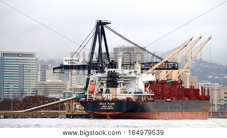 Oakland CA - January 09 2017: Bulk carrier BELLE PLAINE loading at Schnitzer Steel terminal at the Port of Oakland. Schnitzer Steel recycles scrap metal into finished steel products such as rebar and wire rod.