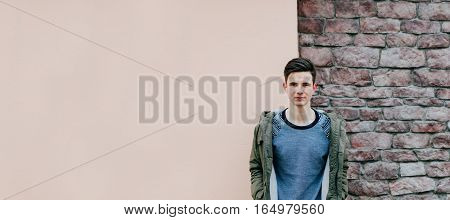 Young man in jacket on the pink and bricks half wall background, photo with place for text