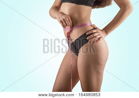 Pretty girl measure her body with a meter