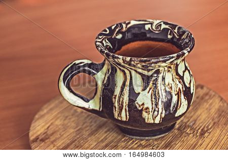 Hand made ceramic cup with hand made ornament on the table.