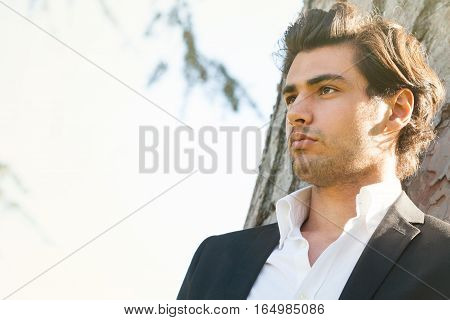 Handsome young italian man portrait, stylish hair. Behind him the trunk of a tree. Outdoors.