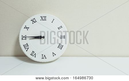 Closeup white clock for decorate show a quarter to nine or 8:45 a.m. on white wood desk and cream wallpaper textured background with copy space
