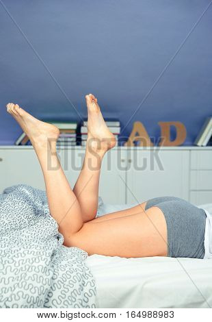 Close up of beautiful woman legs lying on a bed over a bedroom background