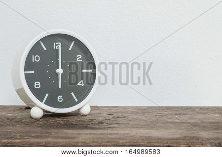 Closeup black and white alarm clock for decorate in 6 o'clock on old wood desk and white cement wall textured background with copy space