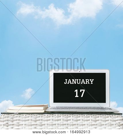 Closeup computer laptop with january 17 word on the center of screen in calendar concept on blurred wood weave table and book on blue sky with cloud textured background with copy space