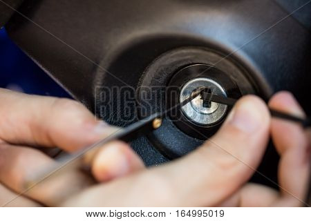 Close-up Of A Person's Hand Inserting Lockpickers Tools In Key Hole