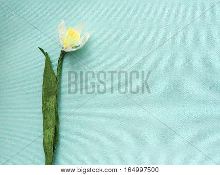 Artificial flower. Handmade paper narcissus on light blue background. Horizontal. Copy space for your text.