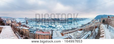 Budapest Hungary - Panoramic skyline view of Budapest with the icy River Danube and Chain Bridge and other landmarks taken from the Buda Castle (Royal Palace) at winter time