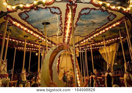 old carousel in night lights that shine yellow lamps