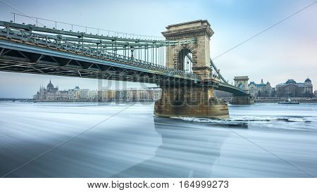 Budapest Hungary - The famous Szechenyi Chain Bridge on the icy River Danube on a cold winter morning with Hungarian Parliament at the background