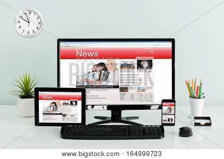 Computer Desktop With Digital Tablet And Mobilephone Showing Online News On Office Desk