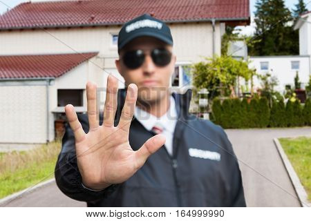 Confident Security Guard Making Stop Gesture Outside The House