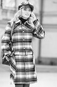 Beautiful young blond in a coat talks on the phone. Photography for fashion brand Catalog clothes poster