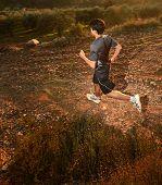 Постер, плакат: Бегун движущихся через освещенной пейзаж contrejour освещение