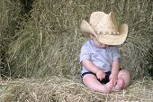 stock photo of baby cowboy  - a baby boy sitting on hay bales wearing a cowboy hat - JPG