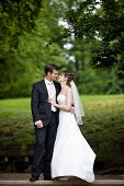 young wedding couple - freshly wed groom and bride posing outdoors on  their wedding day (color tone