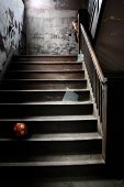 The Stairwell, a child peeks around the corner of the banister at the stairs littered with broken gl