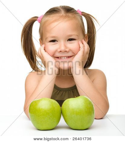 Portrait of a cute little girl with two green apples, isolated over white