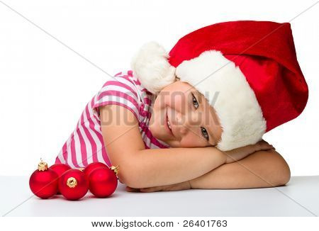 Cute little girl is sitting at table wearing santa hat, isolated over white