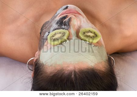 Woman lying down on her back in spa, with special facial mask applied on her face. The mask consist of three colors, each cover different part and eyes are covered by slice of kiwi