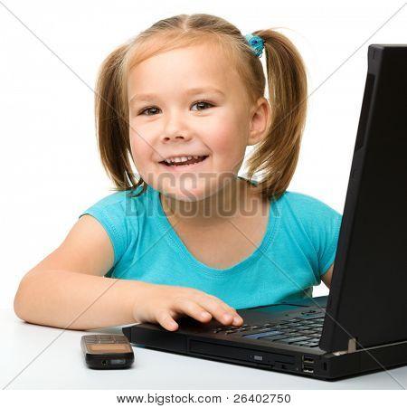Niña linda está sentado en la mesa con su ordenador portátil negro, aislado en blanco