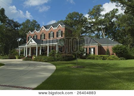New red brick Colonial style house exterior with porch