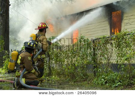 Firefighters battle house on fire