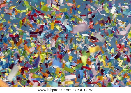 Festive thick colorful confetti against blue sky background