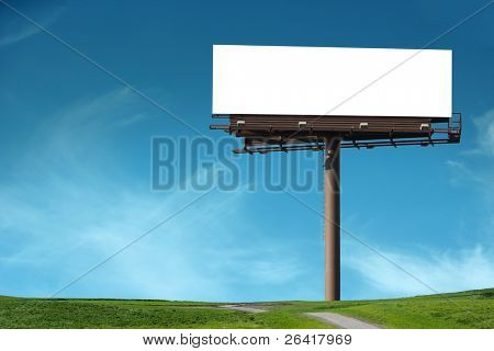 Blank billboard in a field with a blue sky