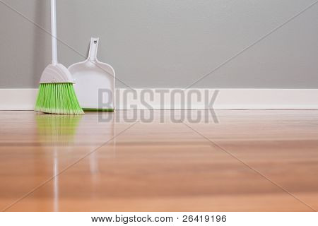 A broom and dust pan on New Hardwood Flooring