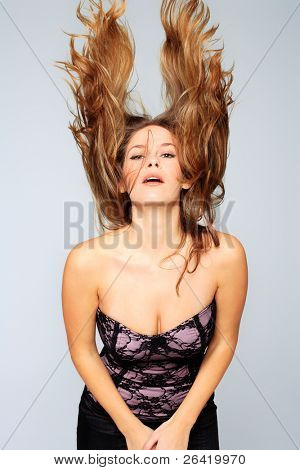 Beauty model in studio with hair blown by wind over gray background