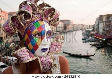 Venice. Italy - Woman with carnival mask in Venice, in background Grand Canal