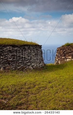Acient stone houses of Easter Island facing Pacific Ocean
