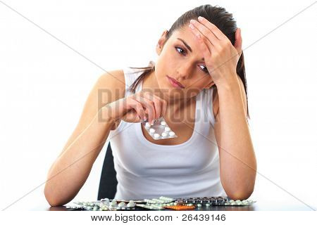 stressed attractive young brunette take some pills, holds glass of water, isolated on white