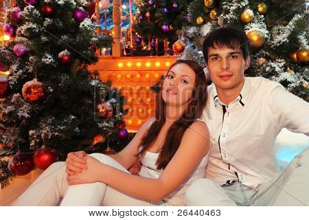 Young man and woman wearing white shirts sit near green trees in snow with Christmas balls