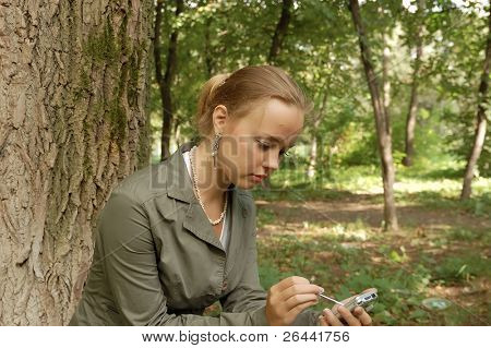 Beautiful girl sitting on a park with smile look at PDA computer