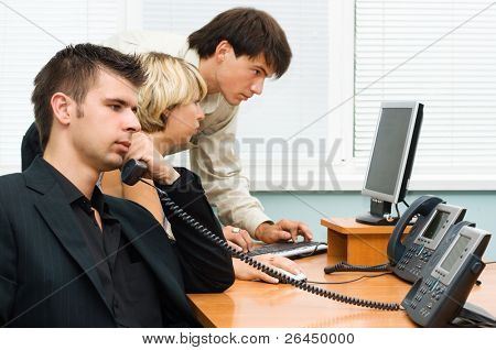 Young businessman making a phone call, with his team working in the background