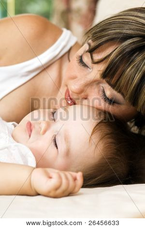 Lovely mother with her little daughter sleeping in the bed