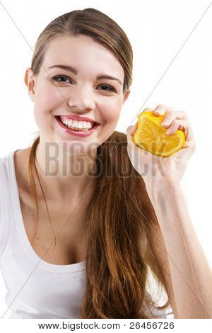 Attractive young woman squeezing and orange, white background