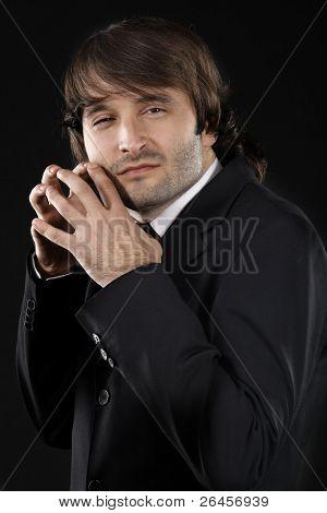 Sly man in elegant suit against black background