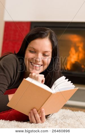 Happy young woman lying by fireplace on carpet reading book