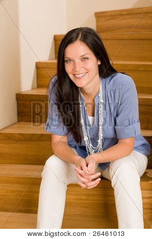 Home living happy beautiful woman sitting on stairs smiling