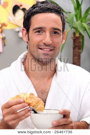 Man dipping croissant in coffee