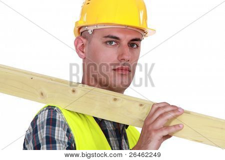 Labourer carrying a wooden plank