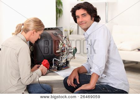 Couple repairing broken television
