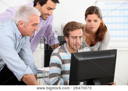 Colleagues around computer
