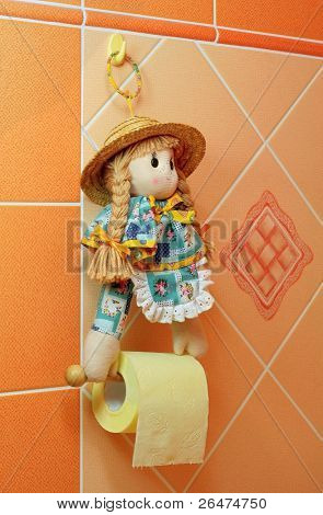 Doll as clamp holder of yellow toilet paper